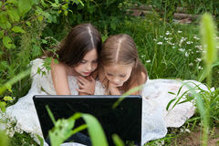 Due bambine che parlano dietro un computer Immagini Stock Libere da Diritti