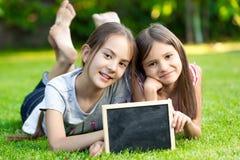 Due bambine che posano sull'erba con la lavagna in bianco Fotografia Stock Libera da Diritti