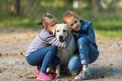 Due bambine con il cane all'aperto giochi Immagini Stock