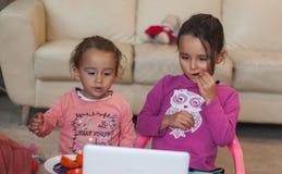 Due bambine con il computer portatile a casa fotografia stock