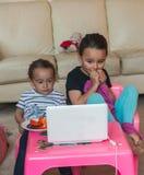 Due bambine con il computer portatile a casa immagini stock