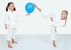 Due bambine con la palla blu battono una gamba di scossa di karatè Immagine Stock Libera da Diritti