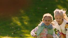 Due bambine felici che corrono attivamente sul prato verde Colpo del primo piano stock footage