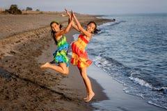 Due bambine felici che saltano nell'aria sulla spiaggia Fotografia Stock