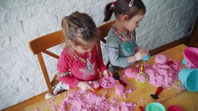 Due bambine giocano con la sabbia cinetica sulla tavola stock footage