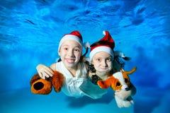 Due bambine nuotano underwater con un cane di piccola taglia in sue mani, esaminando la macchina fotografica e la risata Ritratto immagine stock libera da diritti