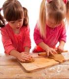 Due bambine occupate che impastano e che rotolano Fotografia Stock Libera da Diritti