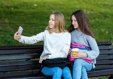 Due bambine sono scolare di estate sul banco Mani che tengono telefono Fotografie su uno smartphone Nell'archivio di Immagine Stock