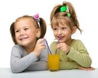Due bambine stanno bevendo il succo di arancia Fotografia Stock