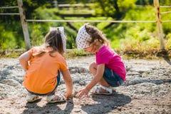 Due bambine stanno giocando con le pietre Immagini Stock