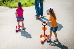 Due bambine sui motorini Immagini Stock