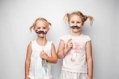 Due bambine sveglie con i baffi di carta mentre posando contro il fondo bianco Fotografie Stock