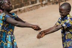 Due bambini africani che puliscono le mani all'aperto con l'acqua dolce Fotografia Stock Libera da Diritti