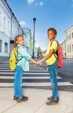Due bambini africani si tengono per mano, stanno la strada trasversale vicina Fotografie Stock