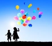Due bambini all'aperto che tengono i palloni Fotografia Stock