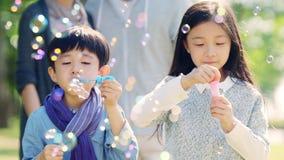 Due bambini asiatici che soffiano le bolle all'aperto nel parco archivi video