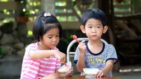 Due bambini asiatici ragazzo e ragazza mangiano il gelato video d archivio