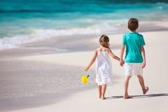 Due bambini che camminano lungo una spiaggia ai Caraibi Fotografia Stock