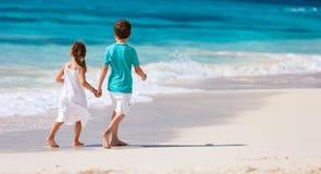 Due bambini che camminano lungo una spiaggia ai Caraibi Immagini Stock