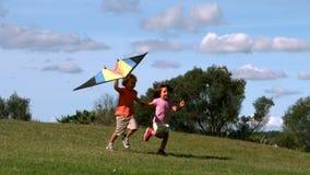 Due bambini che corrono con l'aquilone in parco video d archivio