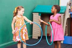 Due bambini che giocano con i hula-hoop fotografia stock