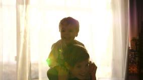 Due bambini che giocano nella stanza Il fratello maggiore tiene il bambino sulle sue spalle, i ragazzi ridono e sorridono archivi video
