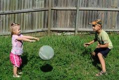 Due bambini che giocano sfera in un cortile immagini stock libere da diritti