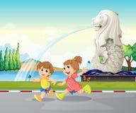Due bambini che giocano vicino alla statua di Merlion Fotografia Stock