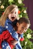Due bambini che hanno divertimento davanti all'albero di Natale Fotografia Stock