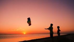 Due bambini che lanciano insieme l'aquilone dell'arcobaleno al tramonto stock footage