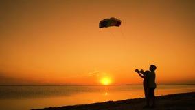 Due bambini che lanciano insieme l'aquilone dell'arcobaleno al tramonto video d archivio