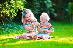 Due bambini che leggono nel giardino di estate Fotografia Stock