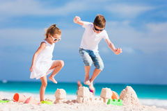 Due bambini che schiacciano castello di sabbia fotografia stock
