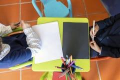 Due bambini che si siedono da piccolo da portare in tavola per disegnare immagine stock libera da diritti
