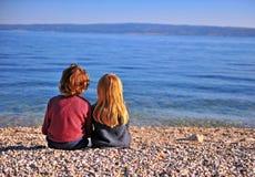 Due bambini che si siedono sulla spiaggia e che esaminano orizzonte fotografia stock libera da diritti