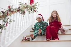 Due bambini che si siedono sulle scale in pigiami al Natale Fotografia Stock