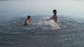 Due bambini che spruzzano acqua in fiume al tramonto archivi video