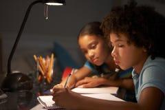 Due bambini che studiano allo scrittorio in camera da letto nella sera Immagine Stock