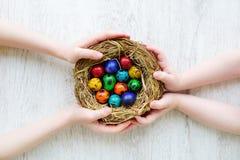Due bambini che tengono un nido con le uova di Pasqua colorate a casa sul giorno di Pasqua Fotografia Stock