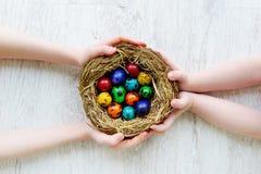 Due bambini che tengono un nido con le uova di Pasqua colorate a casa sul giorno di Pasqua Fotografie Stock