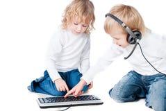 Due bambini con il calcolatore sul pavimento isolato Immagini Stock Libere da Diritti