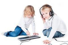 Due bambini con il calcolatore sul pavimento isolato Fotografia Stock