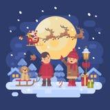 Due bambini con il cane che gioca fuori su una notte nevosa di inverno Fotografia Stock