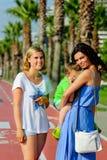Due bambini con la mamma che cammina vicino alle palme nelle vacanze estive Fotografie Stock