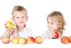 Due bambini con le mele isolate su bianco Fotografia Stock