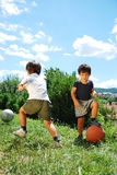 Due bambini con pallacanestro e gioco del calcio Fotografia Stock Libera da Diritti