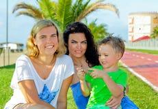 Due bambini con seduta e la risata della mamma Emozioni sincere Immagini Stock Libere da Diritti