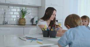 Due bambini dei ragazzi disegnano con sua madre che si siede nella cucina stock footage