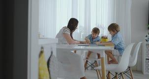 Due bambini dei ragazzi disegnano con sua madre che si siede nella cucina archivi video