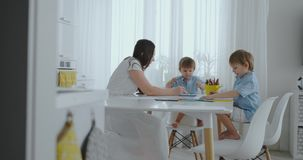 Due bambini dei ragazzi disegnano con sua madre che si siede nella cucina Famiglia felice nel paese video d archivio